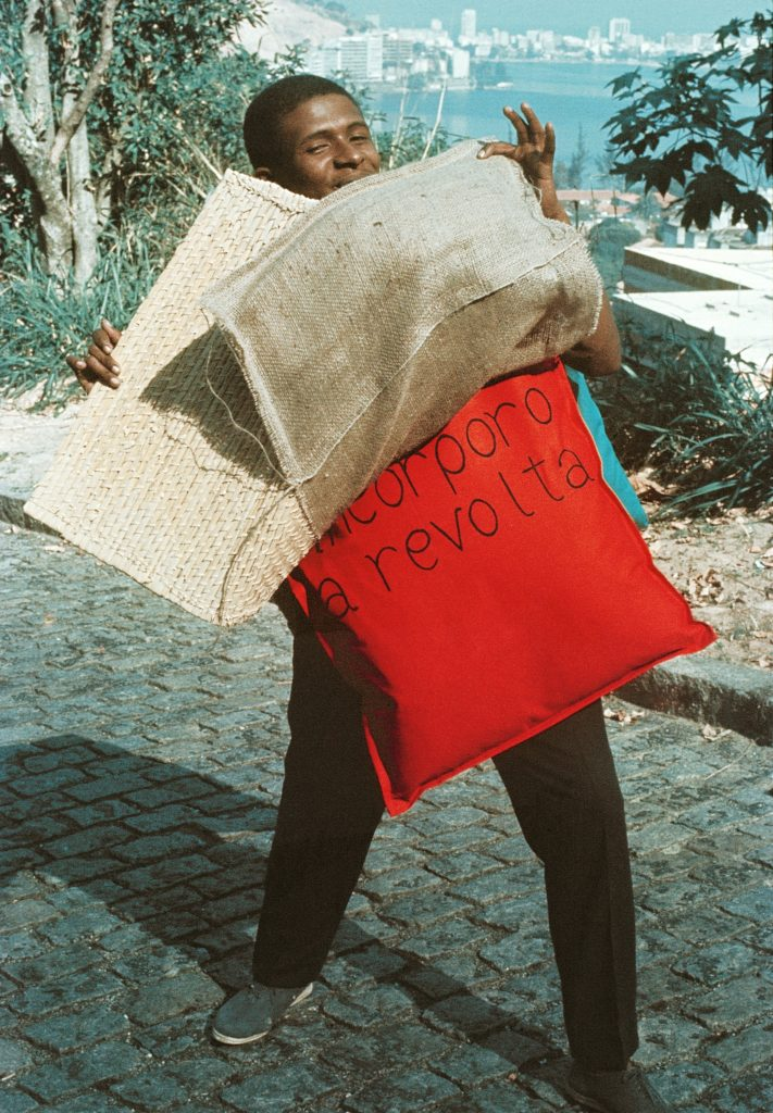 "Nildo of Mangueira wearing ""P15 Parangolé Cape 11, I Embody Revolt (P15 Parangolé capa 12, Eu incorporo a revolta, 1967),"" ca. 1968, Facsimile of photograph, César and Claudio Oiticica, Rio de Janeiro"
