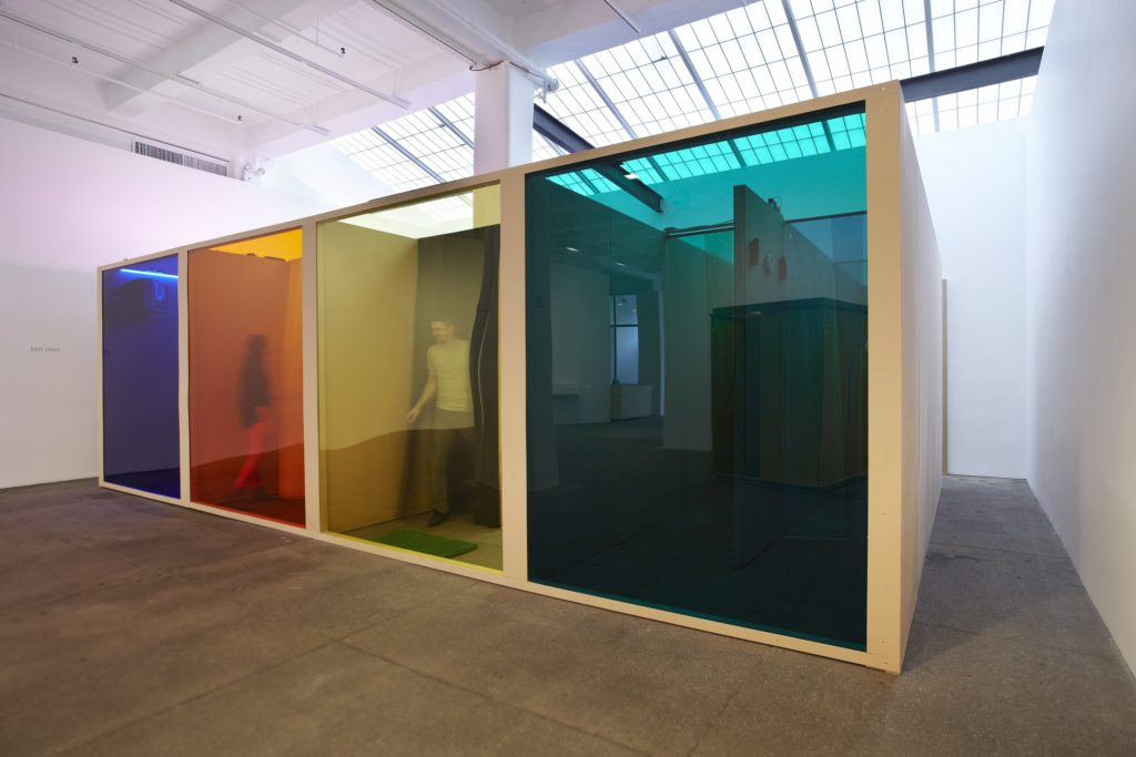 "Hélio Oiticica, ""Filter Project—For Vergara (Projeto Filtro—Para Vergara),"" 1972, nylon, acrylic, plastic curtains, natural fiber doormat, television set, tape recorders, transistor radio, buzzer, orange juice machine, fluorescent lamps, and fiberboard, (c) Projeto Hélio Oiticica, Rio de Janeiro. Courtesy Projeto Hélio Oiticica, Rio de Janeiro and Galerie Lelong, New York"